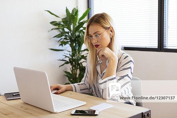 Blonder Büroangestellter am Schreibtisch sitzend  mit Laptop