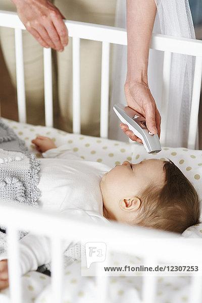 Mutter mit digitalem Thermometer  das die Temperatur des Babys in der Krippe überprüft.