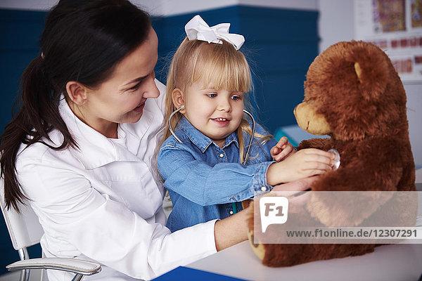 Arzt und Mädchen untersuchen Teddy in der Arztpraxis