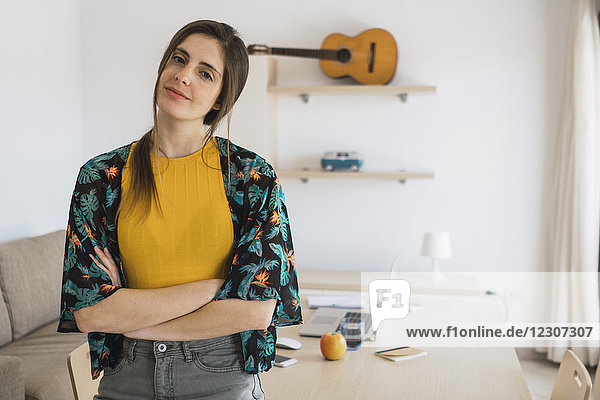 Porträt der lächelnden jungen Frau zu Hause mit Gitarre im Regal Porträt der lächelnden jungen Frau zu Hause mit Gitarre im Regal