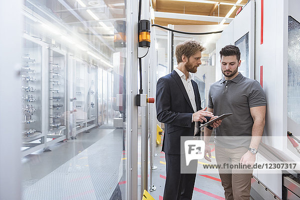 Two men with tablet talking at machine in modern factory