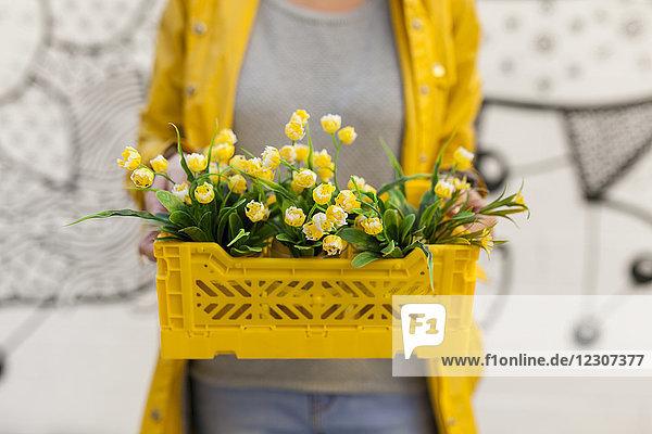 Nahaufnahme einer Frau mit gelbem Frühlingsblumenkasten