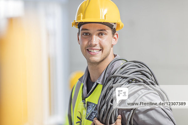 Portrait of smiling electrician with cable on construction site