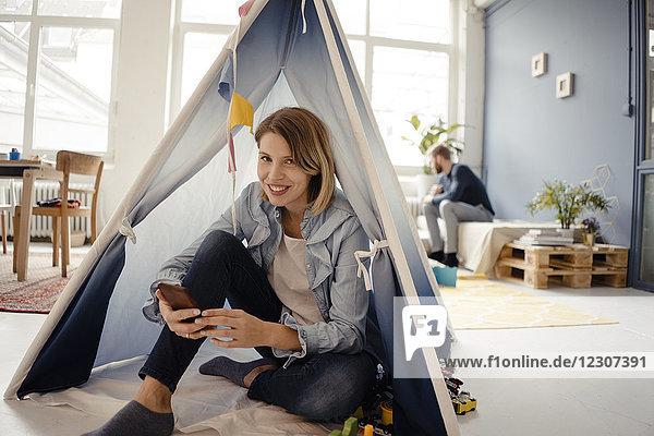 Frau mit Smartphone im Spielzeugzelt  Ehemann im Hintergrund