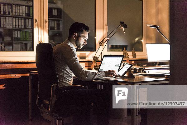 Geschäftsmann  der nachts am Schreibtisch im Büro arbeitet.