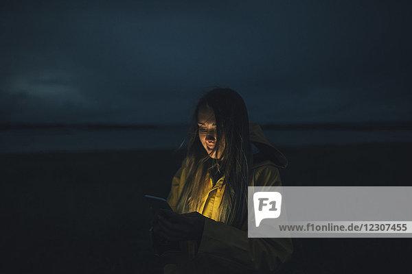 Frankreich  Bretagne  Landeda  Dunes de Sainte-Marguerite  Frau mit Handy am Strand bei Nacht
