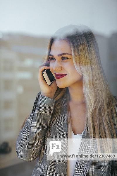 Junge Geschäftsfrau am Fenster stehend  telefonierend
