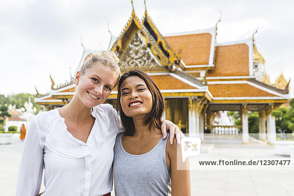 Thailand,  Bangkok,  Porträt von zwei lächelnden Freunden vor dem Tempel