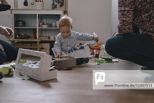 Weihnachtszeit  Junge packt Geschenke aus