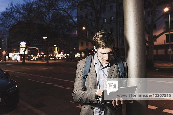 Geschäftsmann mit Laptop in der Stadt bei Nacht