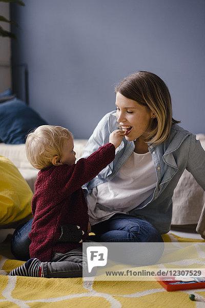 Mutter spielt mit ihrem kleinen Sohn  der sie füttert.