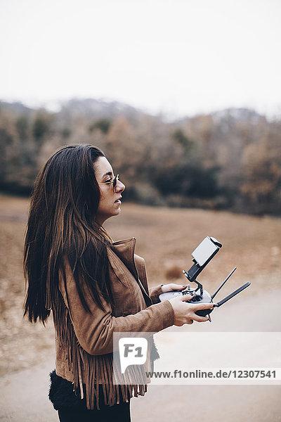 Junge Frau navigiert Drohne mit Fernwirktechnik