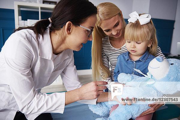 Arzt und Mädchen mit Mutter impfender Teddy in der Arztpraxis