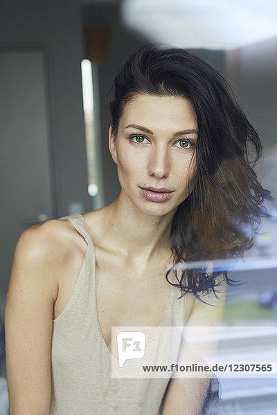 Porträt der attraktiven dunkelhaarigen jungen Frau hinter der Fensterscheibe