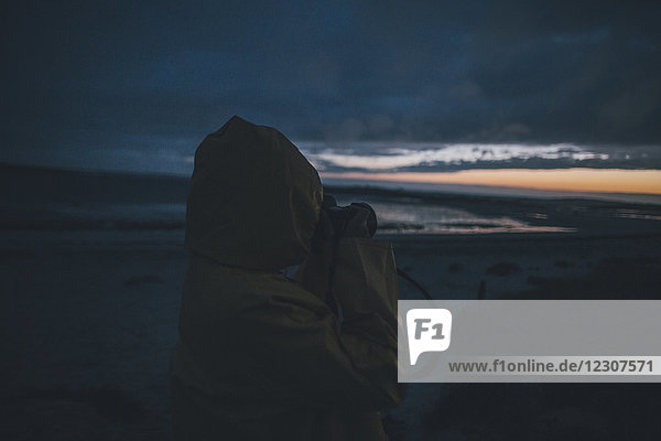 Frankreich  Bretagne  Landeda  Dunes de Sainte-Marguerite  Frau an der Küste beim Fotografieren am Abend