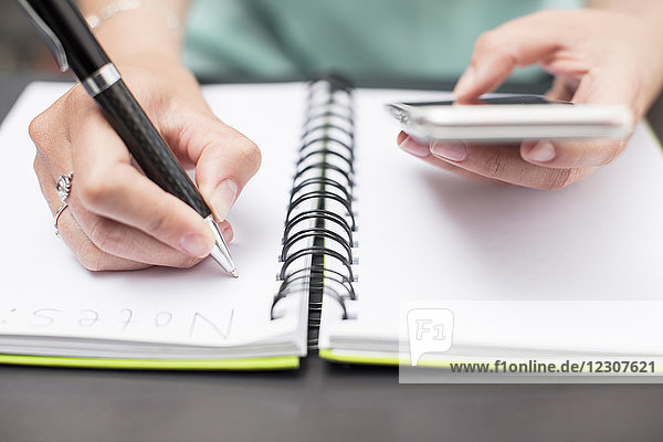 Woman writing notes in diary  holding smartphone