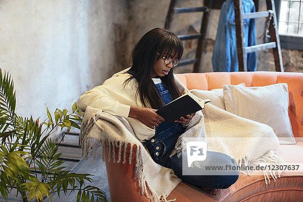 Junge Frau sitzt zu Hause auf der Couch und liest das Buch.