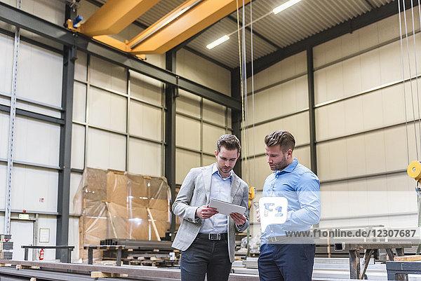 Zwei Geschäftsleute teilen sich das Tablett in der Fabrikhalle.