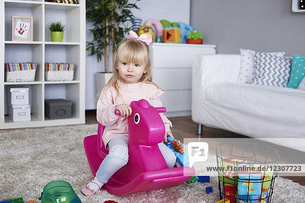Porträt des kleinen Mädchens auf rosa Schaukelpferd im Wohnzimmer