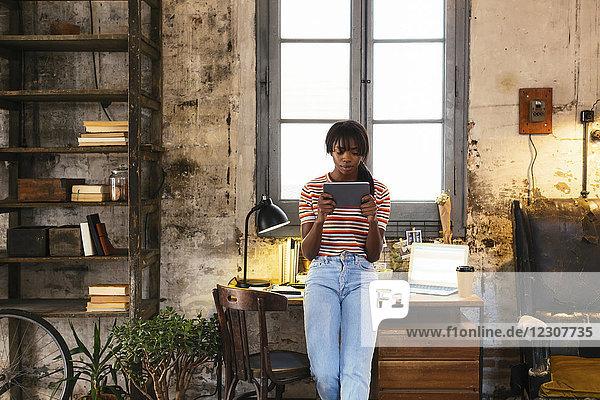 Junge Frau steht vor dem Schreibtisch in einem Loft mit einer Tablette.
