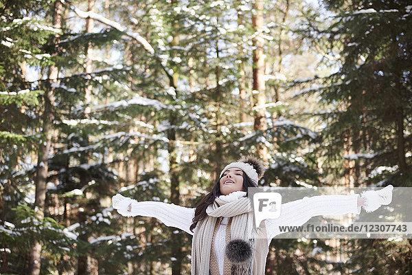 Junge Frau entspannt sich im Winterwald