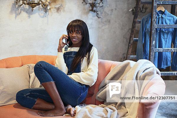 Porträt einer lächelnden Frau am Telefon  die zu Hause auf der Couch sitzt.