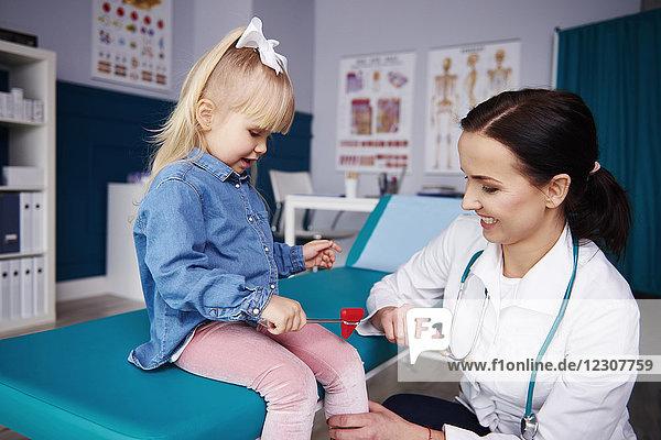 Ärztin untersucht Mädchen in der Arztpraxis