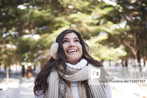 Portrait of happy young woman in winter forest
