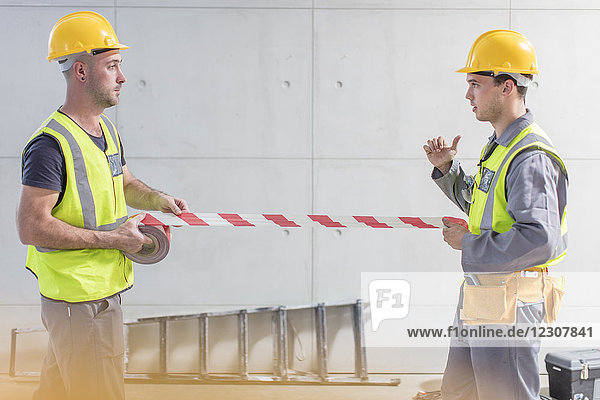 Construction workers using tape on construction site