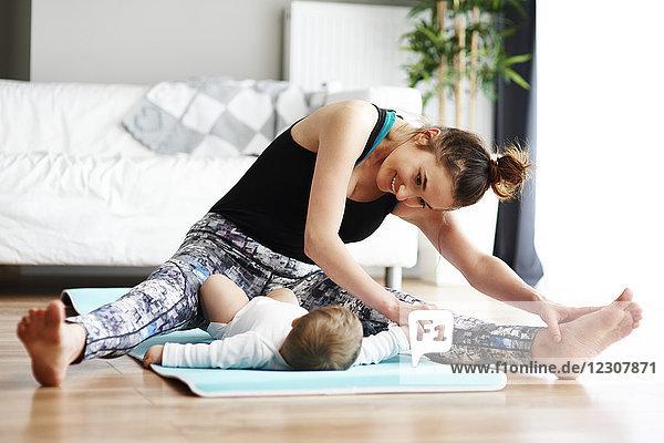 Mutter mit Baby beim Training auf der Yogamatte zu Hause