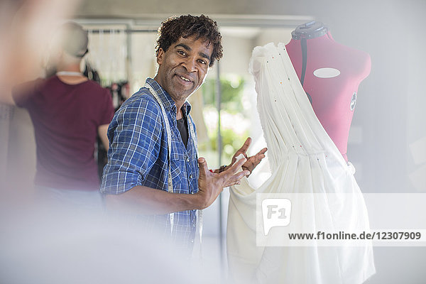 Smiling fashion designer presenting dress