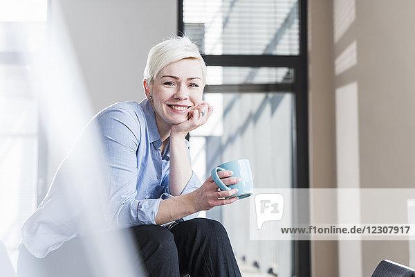 Porträt einer lächelnden Frau  die im Büro auf dem Tisch sitzt.
