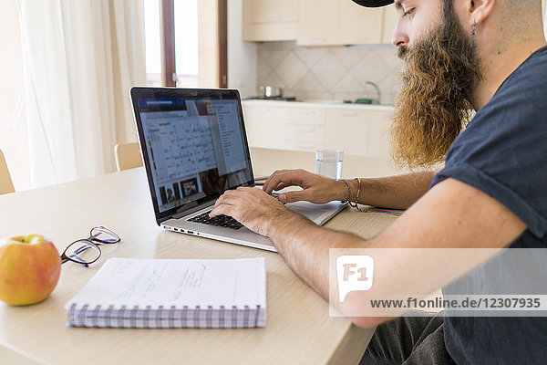 Bärtiger junger Mann  der zu Hause am Laptop arbeitet