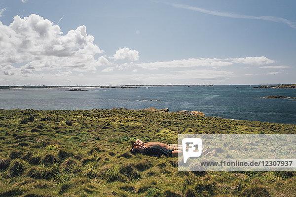 Frankreich  Bretagne  Landeda  Dunes de Sainte-Marguerite  junges Paar im Gras an der Küste liegend