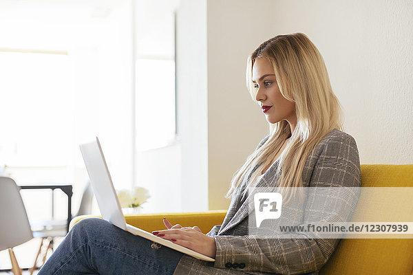 Geschäftsfrau auf gelber Couch sitzend  mit Laptop
