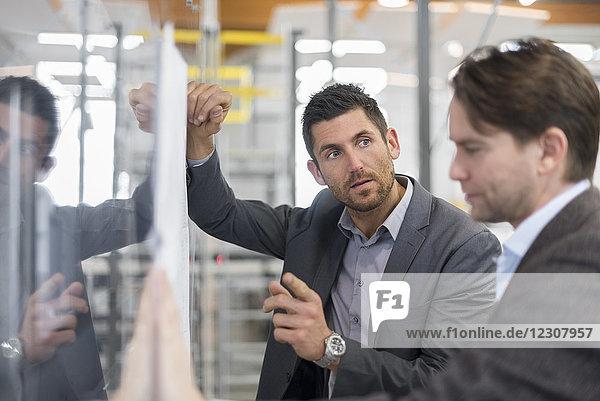 Zwei Geschäftsleute diskutieren über den Plan in einer modernen Fabrik
