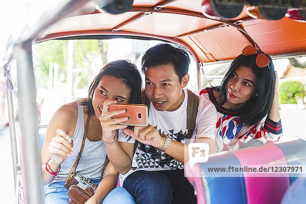 Thailand  Bangkok  drei Freunde auf Tuk Tuk Tuk beim Fotografieren mit dem Smartphone