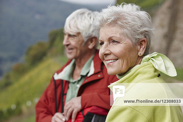 Portrait of happy senior woman with partner in thew background