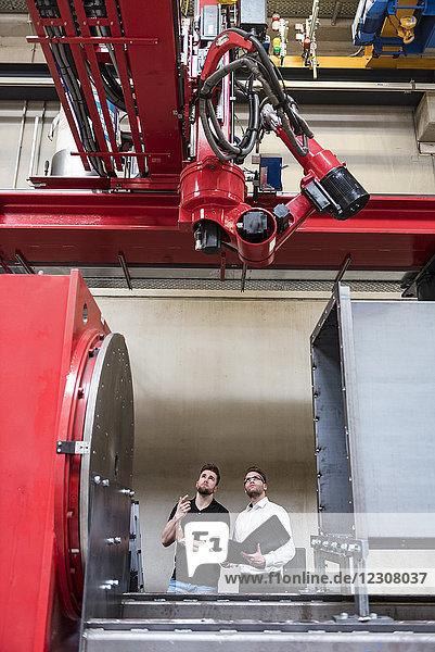 Zwei Männer mit Falzapparat schauen auf die Maschine in der Fabrikhalle