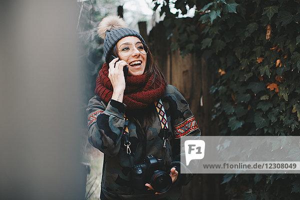 Porträt der lachenden jungen Frau mit Kamera am Telefon
