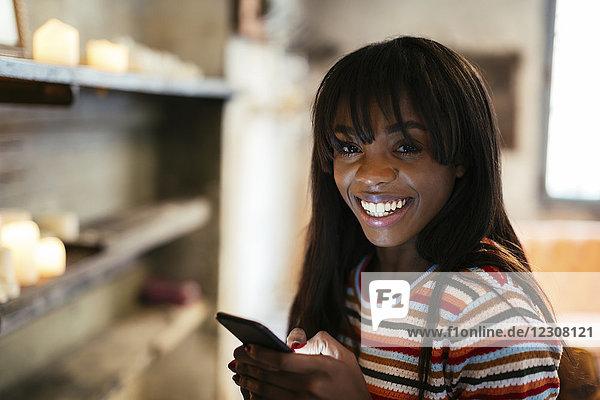 Porträt einer glücklichen jungen Frau mit Handy