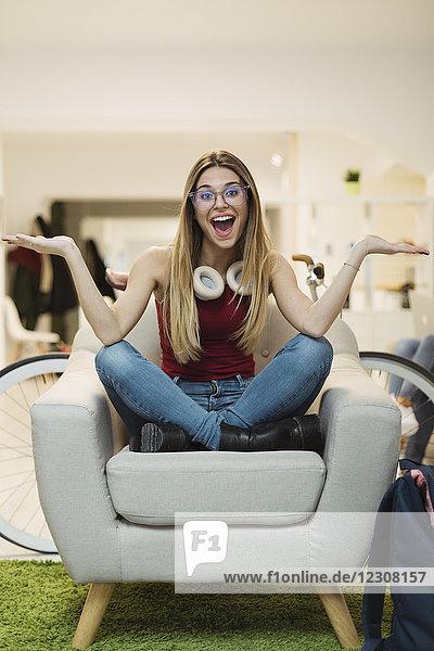 Fröhliche junge Frau sitzt im Sessel im Coworking Space