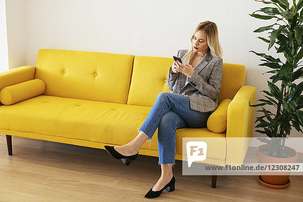 Geschäftsfrau auf gelber Couch sitzend  mit Smartphone