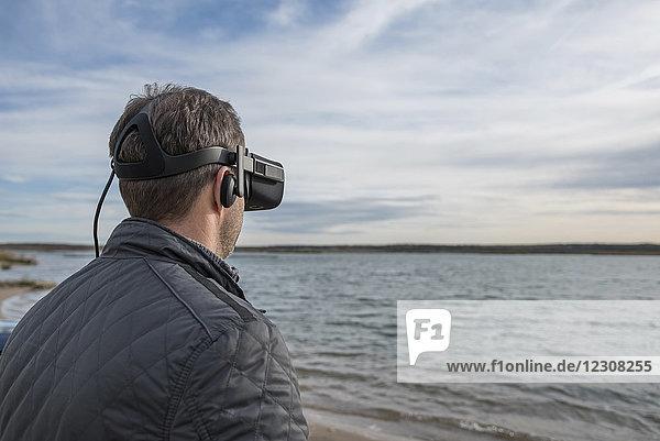Mann mit VR-Brille am Seeufer