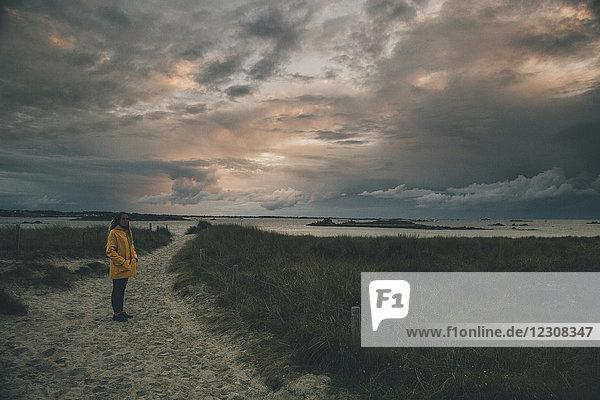 Frankreich  Bretagne  Landeda  Dunes de Sainte-Marguerite  junge Frau steht in der Düne bei Dämmerung
