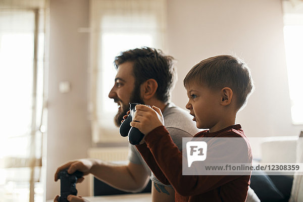 Little boy playing computer game with his father at home
