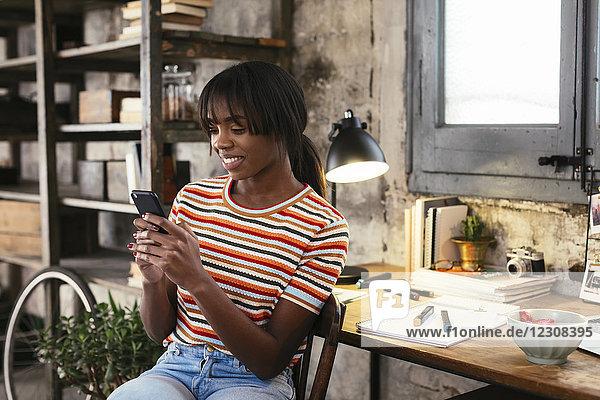 Lächelnde junge Frau sitzt vor dem Schreibtisch in einem Loft und schaut auf das Handy.
