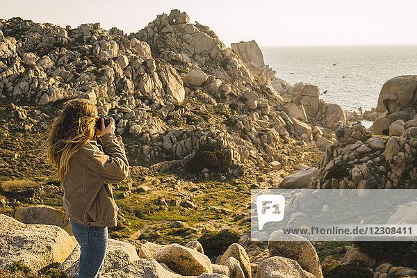 Italien,  Sardinien,  Frau auf einer Wanderung,  die ein Foto an der Küste macht.