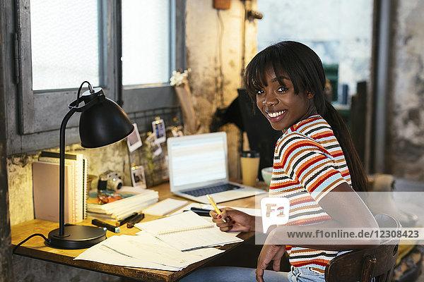 Porträt einer lachenden jungen Frau  die am Schreibtisch in einem Loft sitzt.