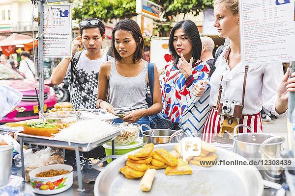 Thailand  Bangkok  Khao San Road  Gruppe von Freunden  die auf dem Straßenmarkt lokale Speisen wählen